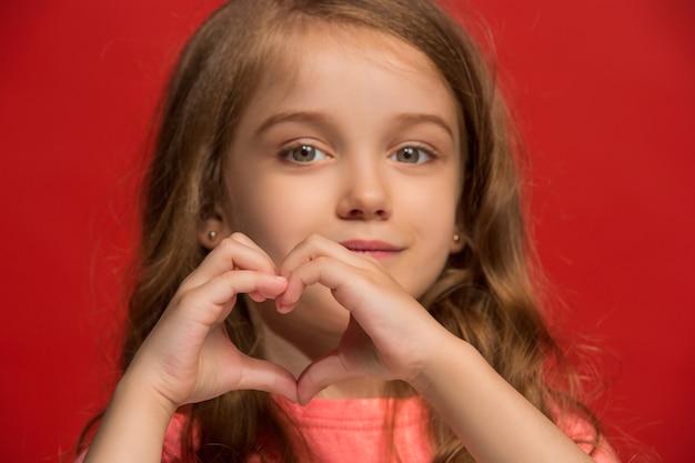Ik hou van je. gelukkig tiener meisje staan, glimlachend geïsoleerd op trendy rood. mooi vrouwelijk portret.