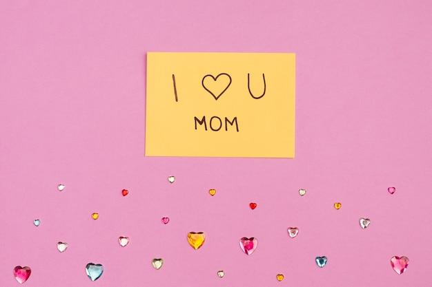 Ik hou van je mama titel op papier in de buurt van decoratieve harten