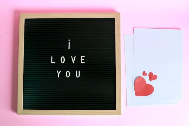 Ik hou van je op letterbord met rode hartvorm op wit papier geïsoleerd op roze achtergrond