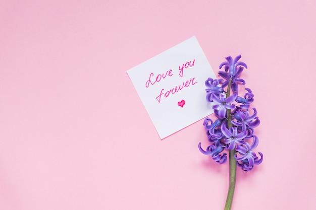 Ik hou van je voor altijd papieren label en paarse hyacint bloem op houten tafel. bovenaanzicht, platliggend
