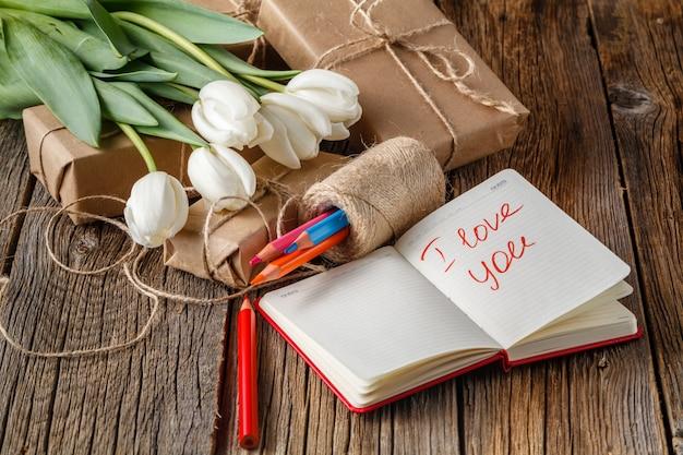 Ik hou van je zin in notitieboekje met bloemen op tafel