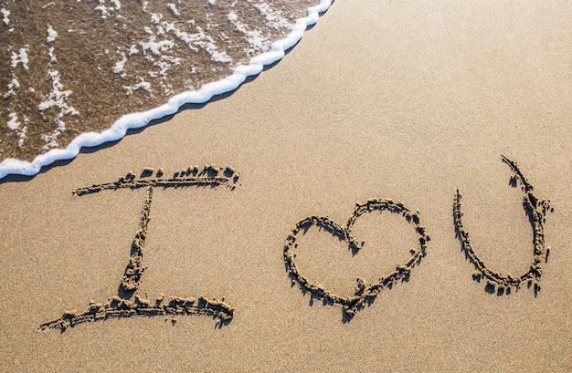 Ik hou van jou. liefde geschreven in het zand