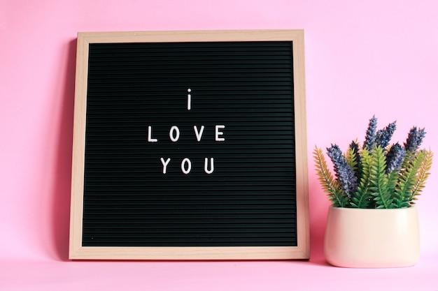 Ik hou van jou op letterbord met decoratieve plant geïsoleerd op roze achtergrond