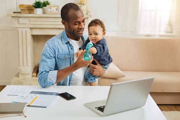 Ik hou van jou. toegewijde liefdevolle jonge afro-amerikaanse vader die zijn zoontje vasthoudt en hem voedt terwijl hij aan tafel zit met zijn laptop