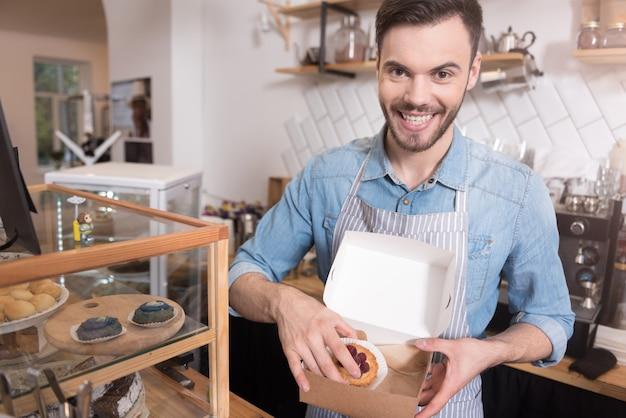 Ik hou van koekjes. tevreden jonge knappe man taarten in de doos glimlachend terwijl hij achter de bar stond.