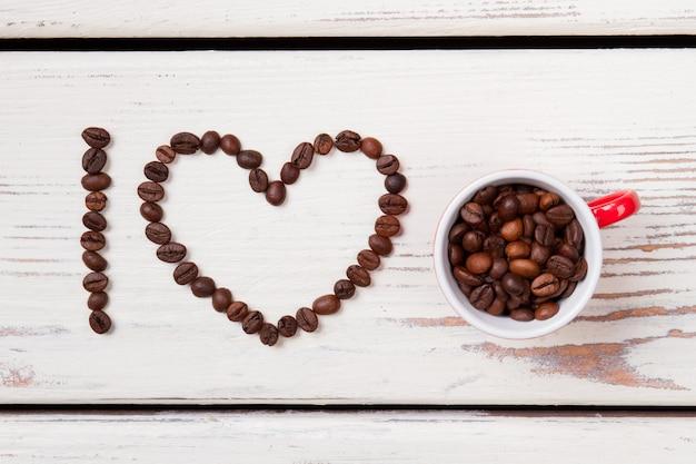 Ik hou van koffieconcept plat gelegd. gebrande koffiebonen gerangschikt in de vorm van een hart en vullende rode kop. bovenaanzicht.