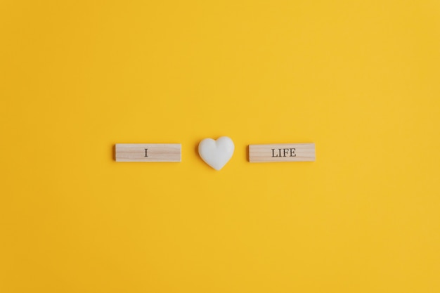 Ik hou van levensteken gespeld op houten pinnen met hartvormig marmer in het midden