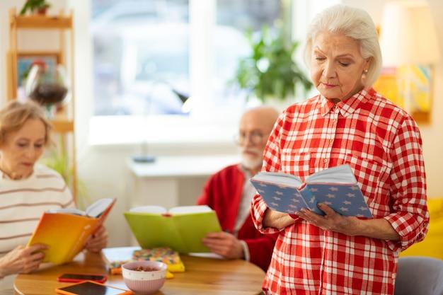 Ik hou van lezen. ernstige grijsharige vrouw die met een boek staat terwijl ze het leest