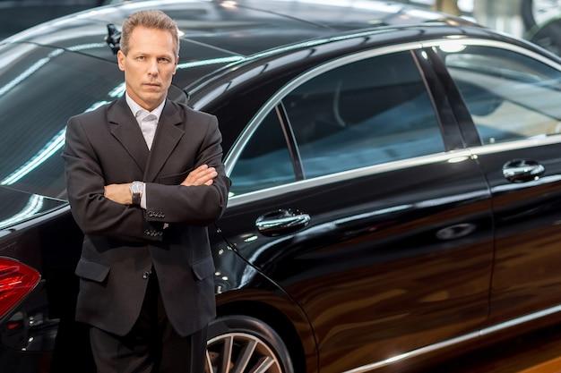 Ik hou van luxe auto's. bovenaanzicht van zelfverzekerde grijze haren man in formalwear leunend naar de auto en kijkend naar de camera