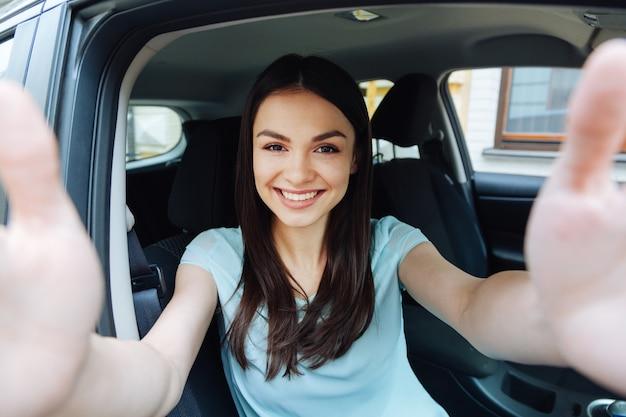 Ik hou van mijn auto. schattige brunette vrouw zitten in de auto