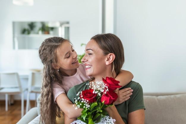 Ik hou van mijn je moeder! aantrekkelijke jonge vrouw met een klein schattig meisje brengt thuis tijd samen door en bedankt voor de handgemaakte kaart met liefdessymbool en bloemen. gelukkig familieconcept. moederdag.