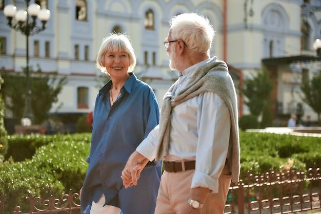 Ik hou van mijn man, een gelukkig en mooi bejaarde echtpaar dat elkaars hand vasthoudt en naar elkaar kijkt terwijl