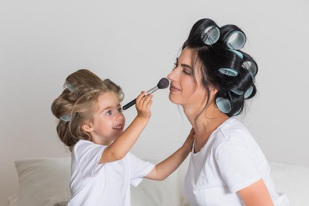 Ik hou van mijn moeder. happy mothers day. mooie moeder met haar kleine schattige dochter heeft plezier thuis. make-up aan elkaar doen en glimlachen.