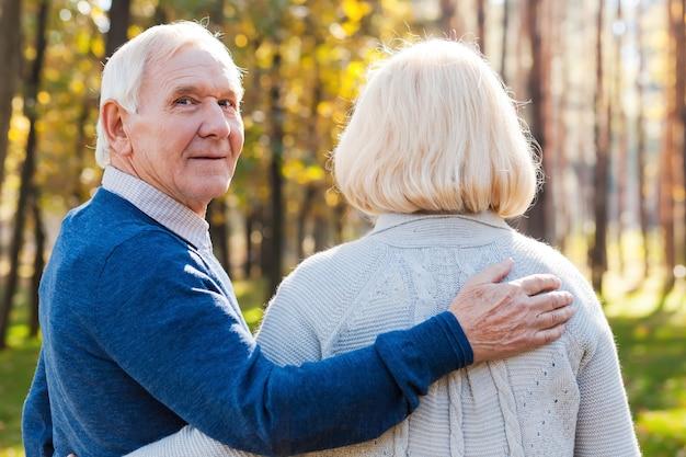 Ik hou van mijn vrouw. achteraanzicht van een gelukkige senior man die over de schouder kijkt en glimlacht terwijl hij met zijn vrouw door het park loopt
