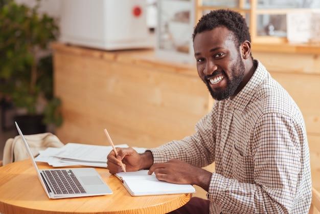 Ik hou van mijn werk. gelukkige jonge man zit aan de tafel in het koffiehuis, maakt aantekeningen in zijn notitieboekje en glimlacht breed naar de camera
