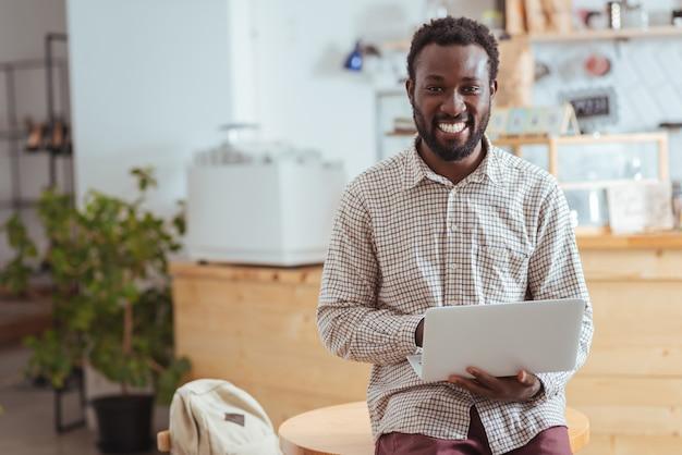 Ik hou van mijn werk. knappe vrolijke man zittend op de tafel in de coffeeshop, met een laptop en poseren voor de camera terwijl hij gelukkig lacht