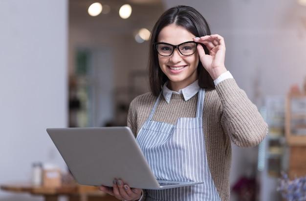 Ik hou van mijn zaken. vrij blij jonge vrouw glimlachend en haar bril aan te raken terwijl laptop vasthoudt.