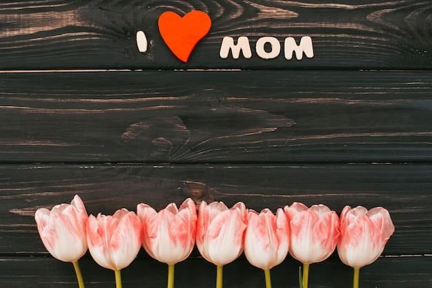 Ik hou van moeder inscriptie met tulpen op tafel