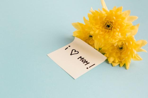 Ik hou van moeder notitie in de buurt van gele bloemen