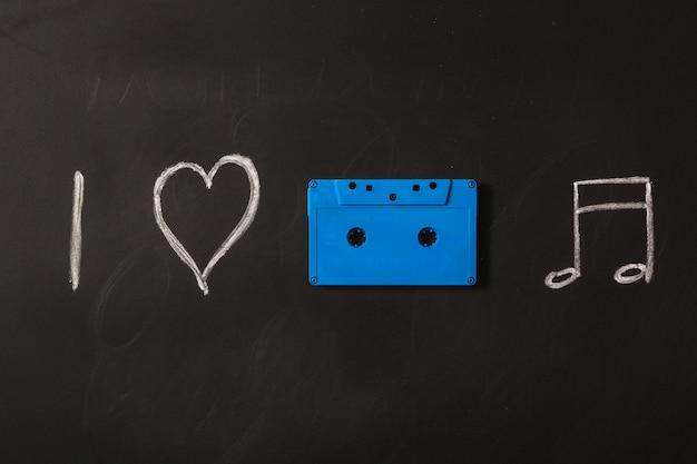 Ik hou van muziek pictogrammen getekend met blauwe cassette op blackboard
