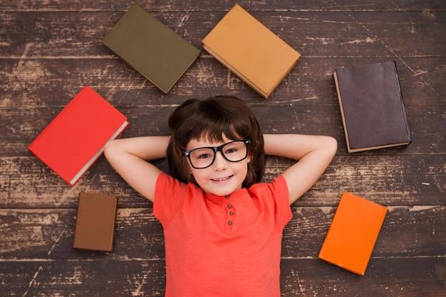 Ik hou van studeren! bovenaanzicht van een kleine jongen die op de grond ligt en lacht terwijl er overal boeken om hem heen liggen
