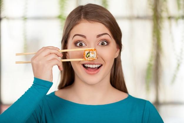 Ik hou van sushi! mooie jonge vrouw die sushi voor haar oog houdt en glimlacht terwijl ze in het restaurant zit