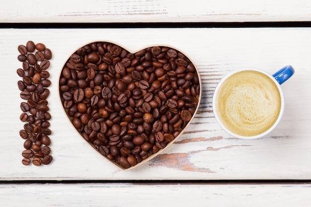 Ik hou van verse ochtend latte met schuim. geroosterde bonen in een vorm van hart en letter i. wit hout op oppervlak.