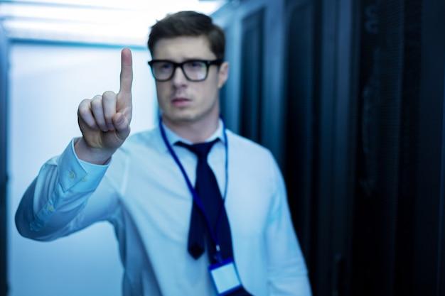 Ik hou van werken. goed uitziende geïnspireerde man die in een datacenter werkt en met zijn vinger wijst