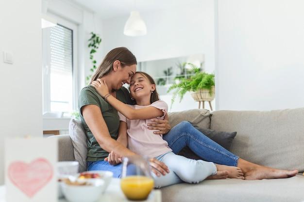 Ik hou zoveel van jou. portret van een gelukkige jonge moeder die een schattig glimlachend dochtertje in de woonkamer meelift, een aanhankelijk schoolmeisje dat de geliefde duizendjarige vrouwelijke oppas of pleegmoeder omhelst