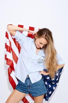 Ik houd van amerika. vrolijk meisje dat een amerikaanse vlag op witte achtergrond houdt. het concept van migratie en van nationale feestdagen en independence day of independence of america 4 juli