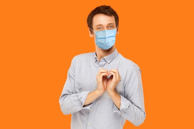Ik houd van je. portret van een vrolijke, gelukkige jonge werkman met een chirurgisch medisch masker dat met een liefdesgebaar van het hart staat en met een glimlach naar de camera kijkt. indoor studio opname geïsoleerd op een oranje achtergrond.