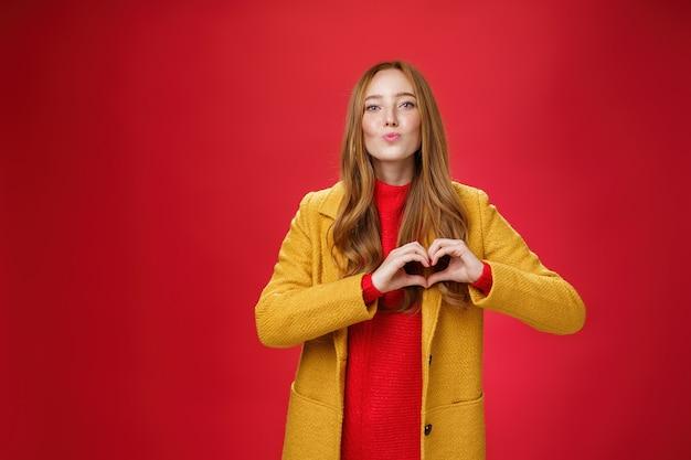 Ik houd van jullie allemaal. portret van romantische en stijlvolle knappe flirterige roodharige vrouw met sproeten en blauwe ogen die lippen vouwen om een kus te geven met een hartgebaar, bekennend in sympathie over de rode muur.