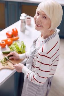 Ik houd van koken. vrolijke oudere vrouw in een schort die voor de camera poseert en vrolijk lacht terwijl ze komkommers snijdt en een salade maakt