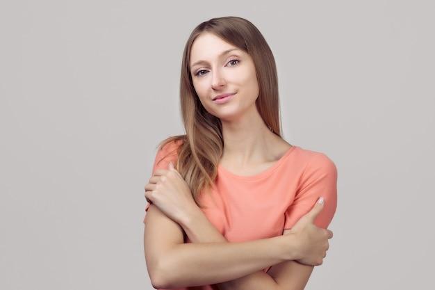 Ik houd van mezelf. portret van zachte mooie mooie jonge vrouw met blonde steil haar knuffelen zichzelf