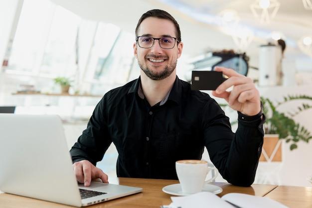 Ik kan alles kopen wat ik wil! vrolijke mannelijke externe werknemer die zijn creditcard toont, naar de camera kijkt en glimlacht. gelukkig man ontving een salaris. hij werkt vanuit café, met behulp van zijn moderne laptop.