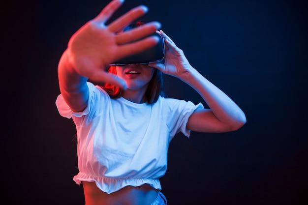 Ik kan dat zien. jonge vrouw met behulp van virtual reality-bril in de donkere kamer met neonverlichting