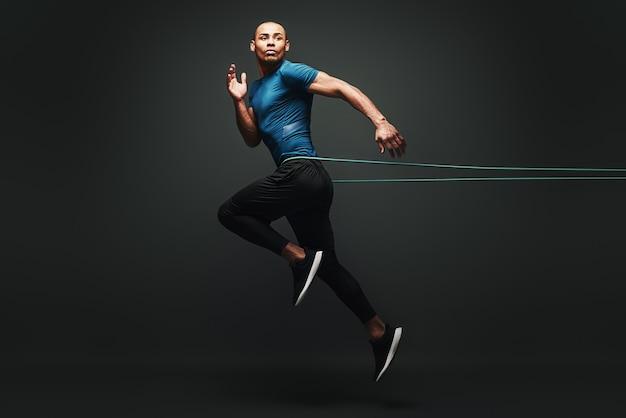 Ik kan het sportman springen met weerstandsband over donkere achtergrond wegkijkend