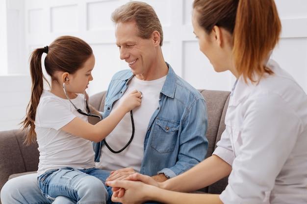 Ik kan je horen ademen. leuke charmante uitstekende kinderarts die haar kleine patiënt een stethoscoop leende om de ademhaling van haar vader te controleren
