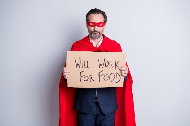 Ik kan je superman zijn. foto van gestresste volwassen zakenman superheld kostuum houd karton plakkaat nodig werk werkkleding pak rood gezichtsmasker mantel geïsoleerde grijze achtergrond