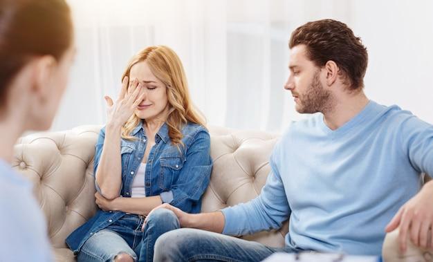 Ik kan mijn gevoelens niet binnen houden. triest depressieve blonde vrouw zittend in het kantoor van de psycholoog en haar gezicht te sluiten tijdens het huilen