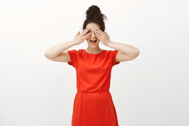 Ik kan niet wachten om verrassing te zien. positieve opgewonden vrouw in een stijlvolle rode jurk, grijnzend en met de handpalmen de ogen bedekkend, gluurend door de vingers