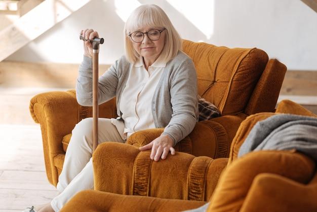 Ik kan niet zonder hem leven. depressieve bejaarde, ongelukkige vrouw die in de fauteuil zit en treurt om haar man terwijl ze zich eenzaam voelt