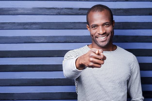 Ik kies jou! gelukkige jonge afrikaanse man die je wijst en glimlacht terwijl hij tegen een gestreepte achtergrond staat