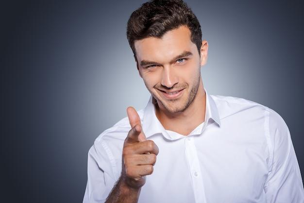 Ik kies jou! knappe jongeman in wit overhemd die naar de camera kijkt en je wijst terwijl hij tegen een grijze achtergrond staat