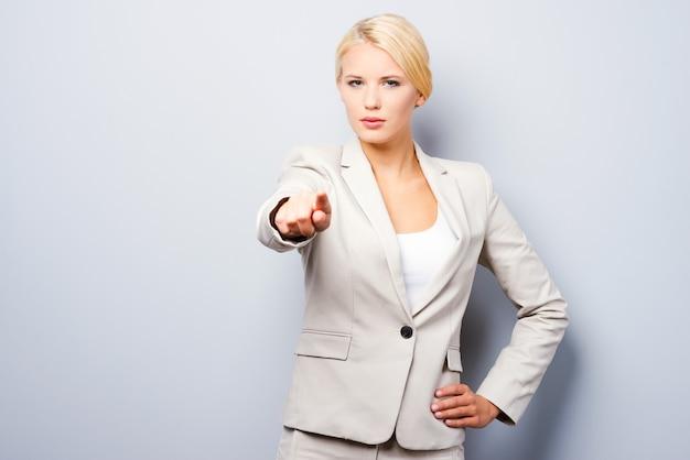 Ik kies jou! mooie jonge zakenvrouw die je wijst terwijl je tegen een grijze achtergrond staat