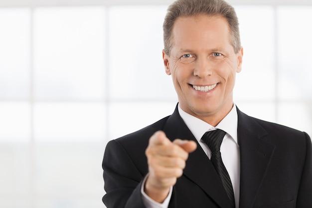 Ik kies jou! portret van een vrolijke volwassen man in formalwear die naar je wijst en glimlacht