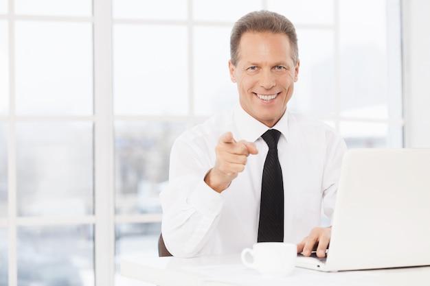 Ik kies jou! vrolijke volwassen man in overhemd en stropdas die camera aanwijst en glimlacht