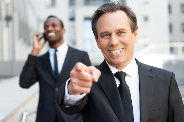 Ik kies jou! zelfverzekerde senior man in formalwear die je wijst en glimlacht terwijl de afrikaanse man op de achtergrond op de mobiele telefoon praat