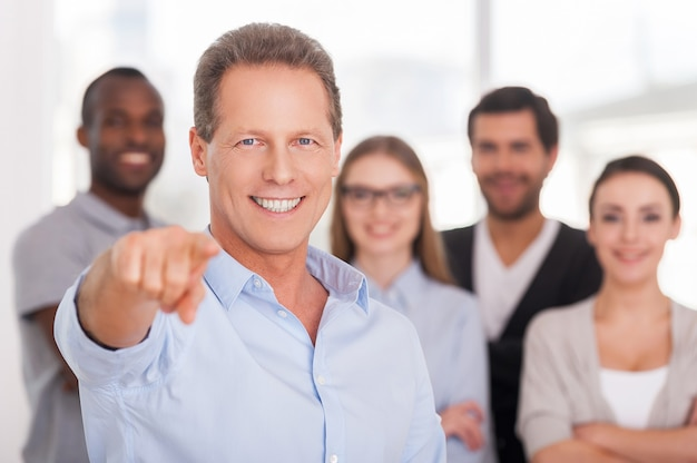 Ik kies jou! zelfverzekerde volwassen man die je wijst en glimlacht terwijl een groep mensen in vrijetijdskleding op de achtergrond staat