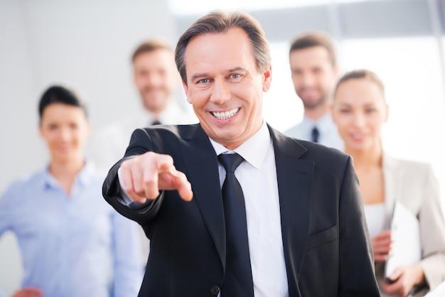 Ik kies jou! zelfverzekerde volwassen zakenman die je wijst en glimlacht terwijl zijn collega's op de achtergrond staan